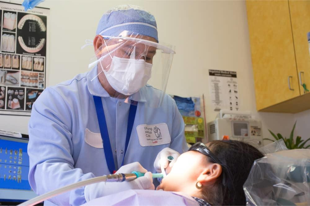 Provider cleaning patients teeth at LifeLong Pinole Dental Care