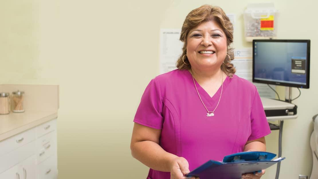 Mrs. Flores smiling while holding clipboard
