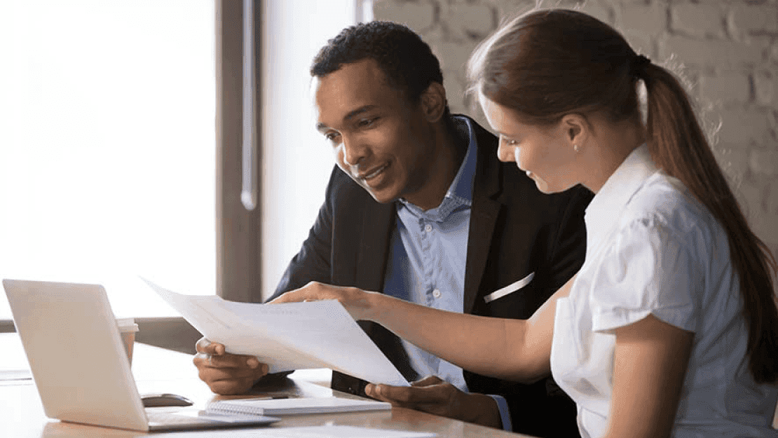 Couple at a computer reviewing paperwork