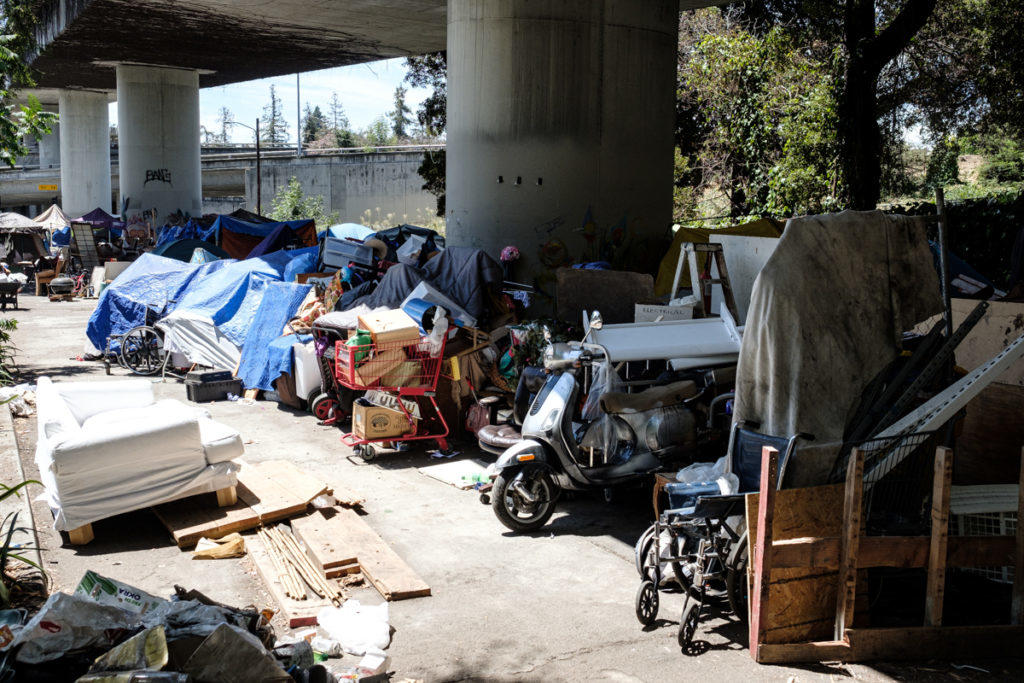 A walkway carves through rows of tents and various found items at the homeless encampment under the MacArthur overpass at Harrison. July 11, 2020. Photo: Pete Rosos