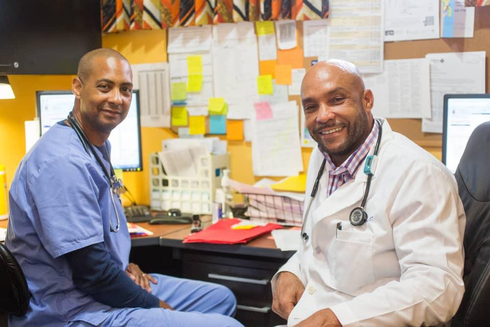 Two Providers Sitting at Desk Smiling